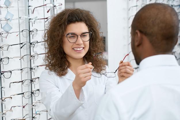 Vue arrière d'un homme essayant des lunettes dans un magasin d'optique. Photo Premium