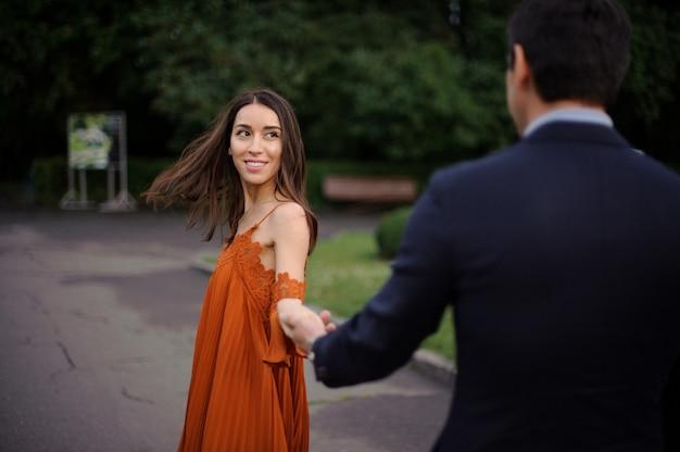 Vue arrière de l'homme est costume tenant la main de la belle femme Photo Premium