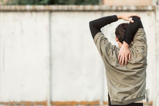 Vue arrière homme faisant des exercices d'échauffement Photo gratuit