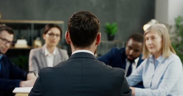 Vue Arrière Sur L'homme De Race Blanche Exécutant La Conférence Des Partenaires Et Des Investisseurs Au Bureau Au Bureau. Photo Premium