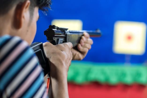 Vue arrière de l'homme avec son pistolet sur tir à la cible dans la pratique tir range, sport et soldie Photo Premium