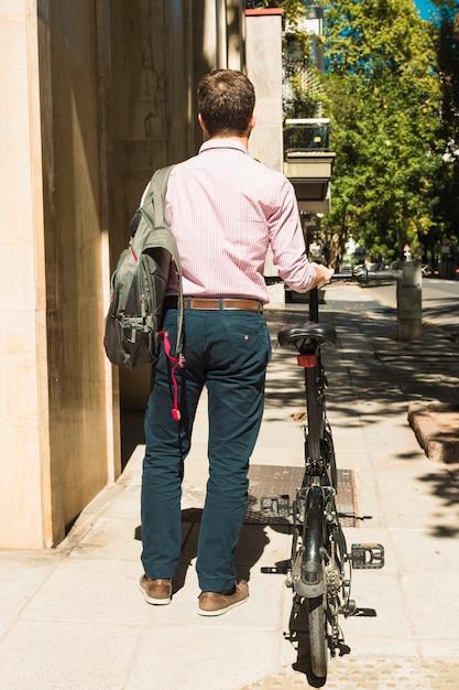 Vue arrière d'un homme avec son sac à dos, marchant à vélo Photo gratuit