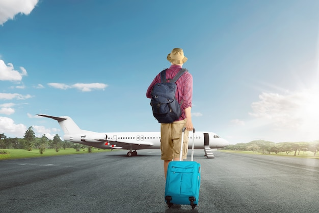 Vue arrière de l'homme voyageur asiatique qui marche avec valise à l'avion Photo Premium