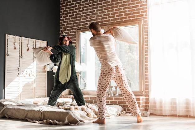 Vue arrière d'un jeune couple se battre avec un oreiller dans la chambre Photo gratuit