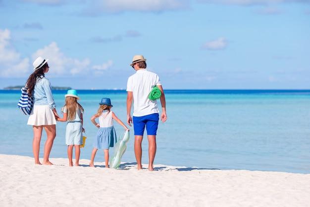 Vue arrière d'une jeune famille sur la plage tropicale Photo Premium