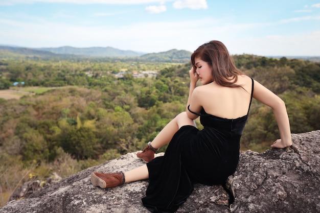 Vue arrière de la jeune femme asiatique en robe noire, assis dans la nature en plein air Photo Premium
