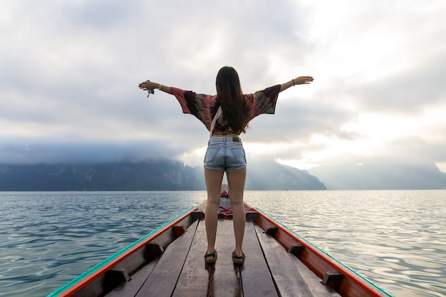Vue Arrière De La Jeune Femme Asiatique Voyageant En Bateau En Bois Au Lever Du Soleil Parmi L'île De Khao Sok Thaïlande Photo Premium
