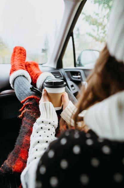 Vue Arrière Jeune Femme Assise Dans Une Voiture Avec Une Tasse De Café Photo Premium