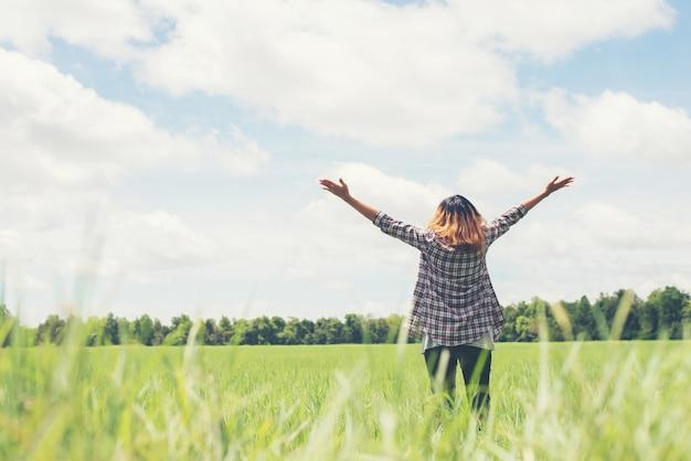 Vue Arrière De La Jeune Femme à Bras Ouverts Dans La Prairie Photo gratuit