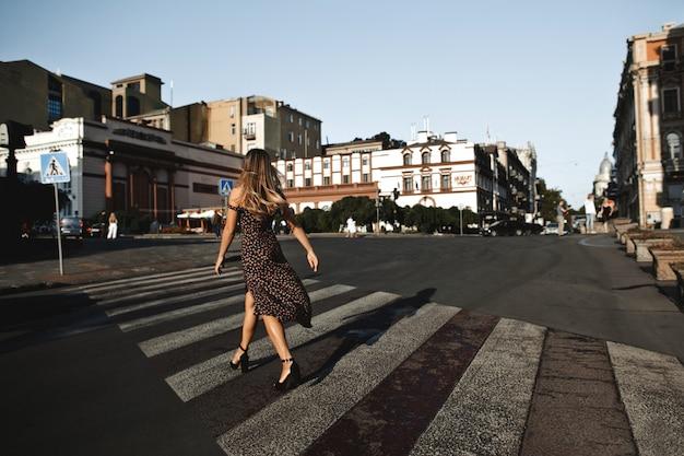 Vue Arrière D'une Jeune Fille En Robe Sur Le Talon Haut Sur L'intersection Vide Dans La Rue De La Ville Photo gratuit