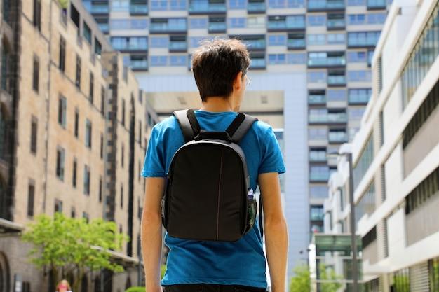 Vue Arrière D'un Jeune Homme Avec Sac à Dos Vient D'arriver Dans Une Grande Ville Et à La Recherche De Bâtiments Modernes Avec Perspectives Et Opportunités Photo Premium