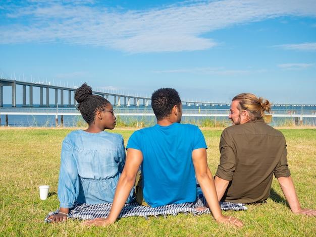 Vue arrière de jeunes amis assis sur l'herbe Photo gratuit