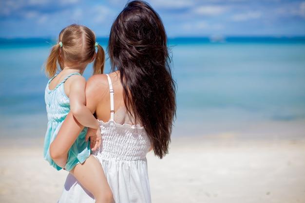 Vue arrière de la mère et sa petite fille à la recherche sur la mer à la plage tropicale Photo Premium