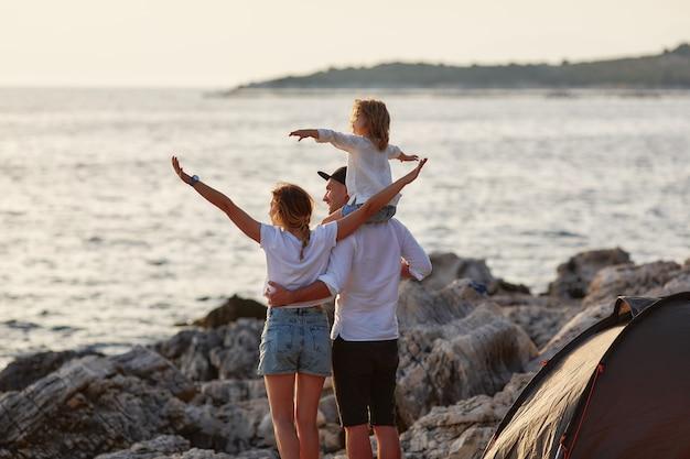 Vue arrière des parents heureux avec la petite fille, assis sur le cou de papa et admirant le soleil couchant sur la mer près de la tente. famille embrassant et pointant à la main à la mer et regardant de près à ce côté. Photo Premium