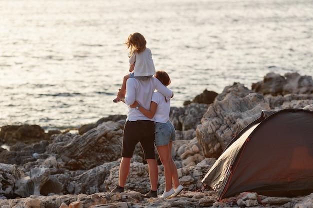 Vue Arrière Des Parents Heureux Avec Petite Fille, Assis Sur Le Cou. Photo Premium