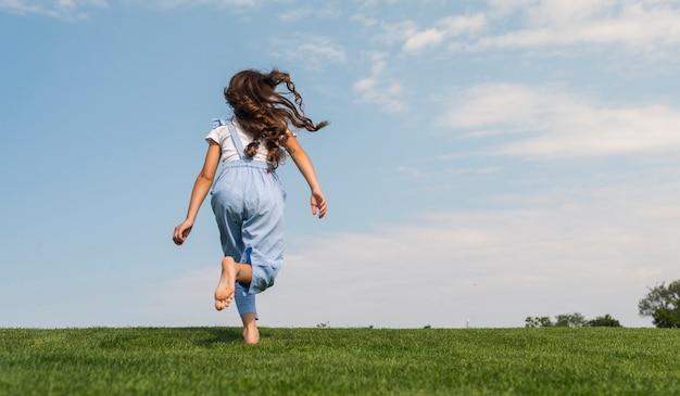 Vue arrière petite fille courir pieds nus Photo gratuit