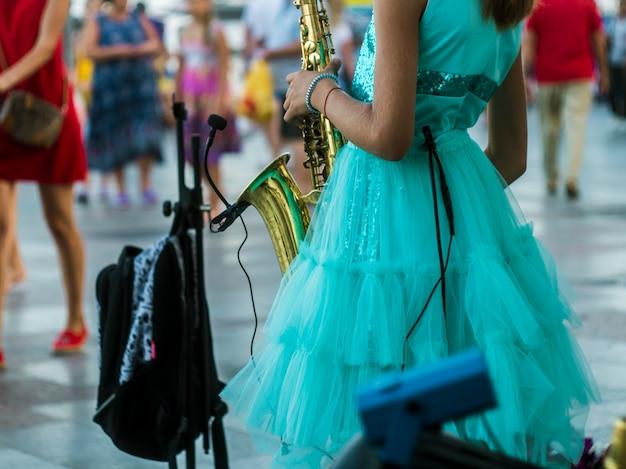 Vue arrière petite fille debout dans la rue bondée et jouant de la musique de saxophone Photo Premium