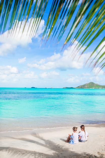 Vue Arrière Des Petites Filles Sur La Plage De Sable. Enfants Heureux Assis Sous Le Palmier Sur La Plage Tropicale Photo Premium