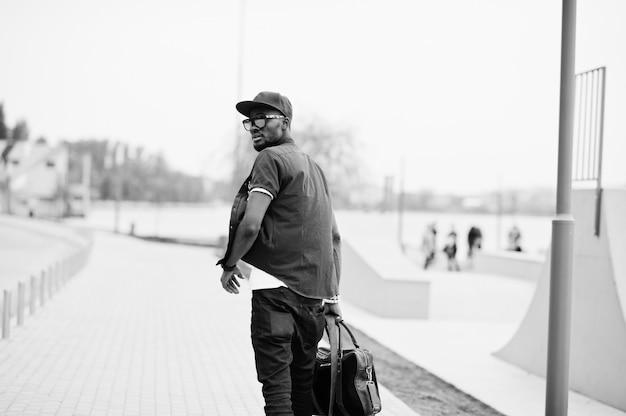 Vue Arrière Portrait De Marche élégant Homme Afro-américain Porter Des Lunettes De Soleil Et Casquette Avec Sac à Main En Plein Air. Homme Noir De Mode De Rue. Photo Premium