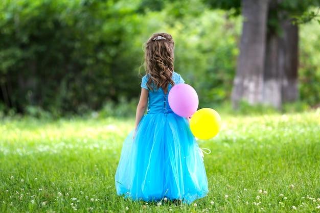 Vue arrière, portrait en pied d'une jolie petite fille aux cheveux longs blonde vêtue d'une longue robe bleue avec des ballons colorés, debout dans un champ fleuri sur des arbres verts floues Photo Premium
