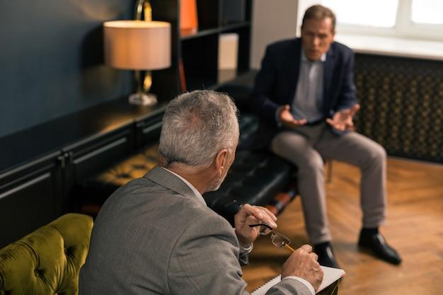 Vue Arrière Portrait D'un Psychothérapeute Senior Assis Dans Un Fauteuil Vert Olive Devant Son Patient Photo Premium