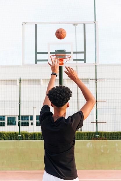Vue arrière, de, sportif, lancer balle, dans, cerceau Photo gratuit