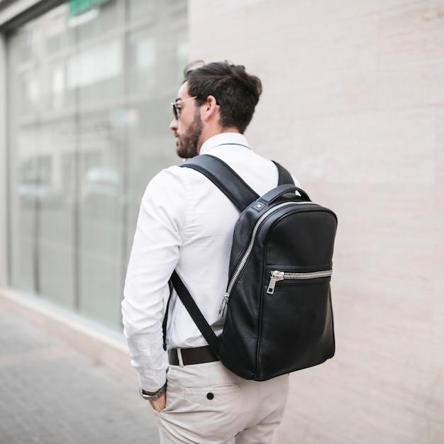 Vue arrière d'un touriste masculin avec sac à dos noir Photo gratuit