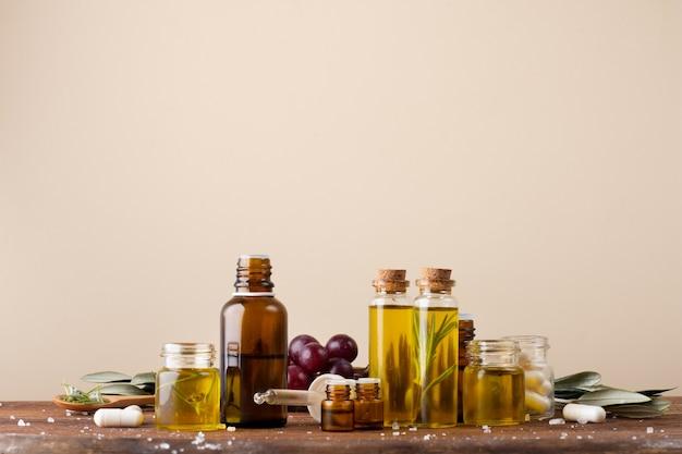 Vue Avant Des Bouteilles En Plastique Avec De L'huile Et Des Médicaments Sur La Table Photo gratuit