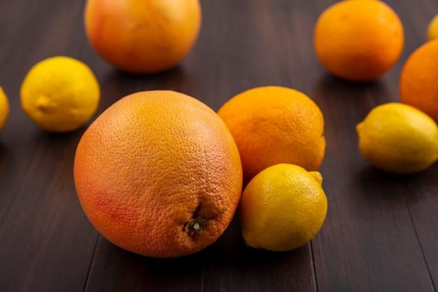 Vue Avant Des Citrons Aux Oranges Et Pamplemousses Sur Fond De Bois Photo gratuit