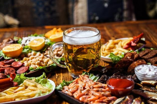 Vue Avant Des Collations à La Bière Avec Des Quartiers De Citron Sur Un Support Avec Un Verre De Bière Photo gratuit