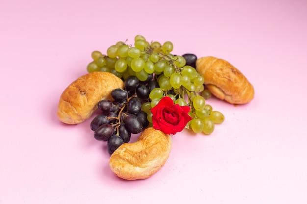 Vue Avant De Délicieux Croissants Cuits Au Four Avec Garniture De Fruits Avec Des Raisins Noirs Et Verts Frais Sur Le Bureau Rose Photo gratuit