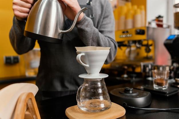 Vue Avant Du Barista Mâle Verser De L'eau Bouillante Dans Le Filtre à Café Photo gratuit