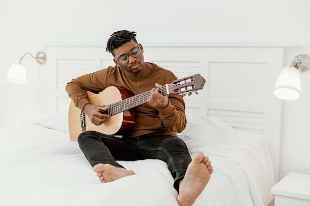 Vue Avant Du Musicien Masculin à La Maison à Jouer De La Guitare Sur Le Lit Photo gratuit