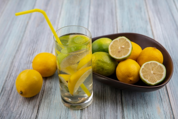 Vue Avant De L'eau De Désintoxication Dans Un Verre Avec Une Paille Jaune Et Citrons Verts Aux Citrons Dans Un Bol Sur Un Fond Gris Photo gratuit