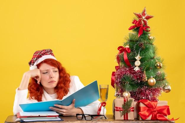 Vue Avant Femme Médecin Assis Derrière La Table De Lecture De Documents Sur Un Bureau Jaune Avec Arbre De Noël Et Coffrets Cadeaux Photo gratuit