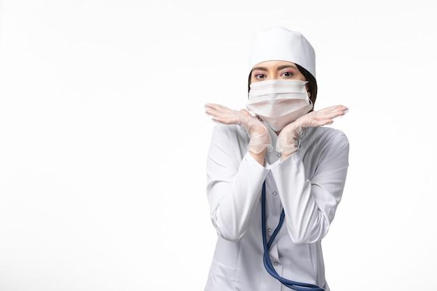 Vue Avant Femme Médecin En Costume Médical Blanc Avec Un Masque En Raison De La Pandémie Posant Sur Le Mur Blanc De La Médecine De La Santé Pandémique Covid- Photo gratuit