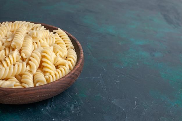 Vue Avant En Forme De Pâtes Italiennes Délicieuses à L'intérieur De Petites Pâtes à L'intérieur De Pot Brun Sur Un Bureau Bleu Foncé Photo gratuit