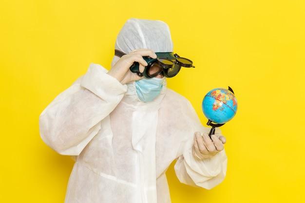 Vue Avant De L'homme Travailleur Scientifique En Costume Spécial Tenant Petit Globe Rond Sur Un Bureau Jaune Photo gratuit