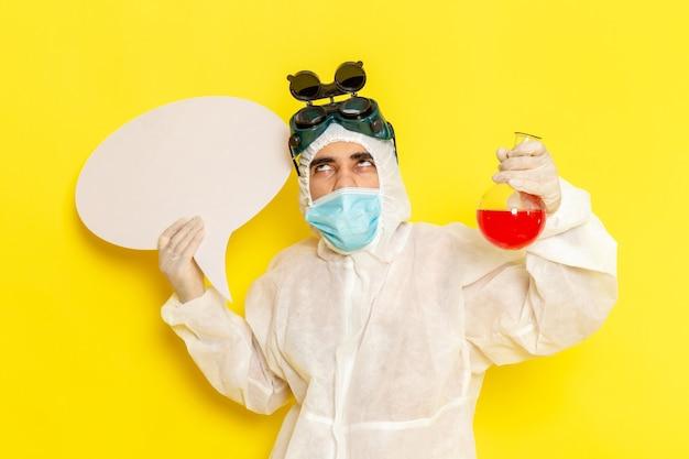 Vue Avant De L'homme Travailleur Scientifique En Tenue De Protection Spéciale Tenant Flacon Avec Solution Rouge Et Panneau Blanc Sur Surface Jaune Photo gratuit
