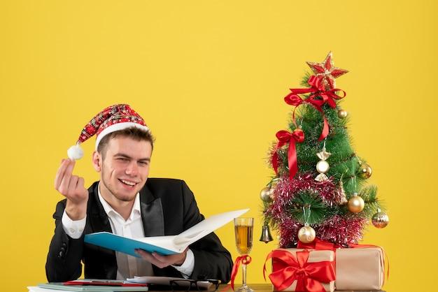 Vue Avant De L'homme Travailleur Tenant Des Documents Autour De Petit Arbre De Noël Et Présente Sur Le Bureau Jaune Travail De Noël Couleur Bureau Nouvel An Photo gratuit