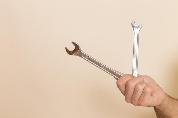 Vue Avant Des Outils D'argent Tenir Par Mâle Sur Fond Blanc Instrument Instrument Mâle Photo gratuit