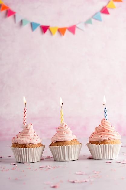 Vue Avant Des Petits Gâteaux D'anniversaire Avec Guirlande Et Bougies Allumées Photo gratuit
