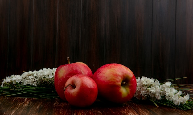 Vue Avant Des Pommes Rouges Avec Des Fleurs Blanches Sur Un Fond En Bois Photo gratuit
