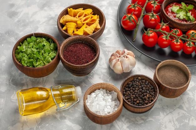 Vue Avant Des Tomates Cerises Fraîches à L'intérieur De La Plaque Avec Différents Assaisonnements Sur Surface Blanche Salade Alimentaire Repas De Légumes Photo gratuit