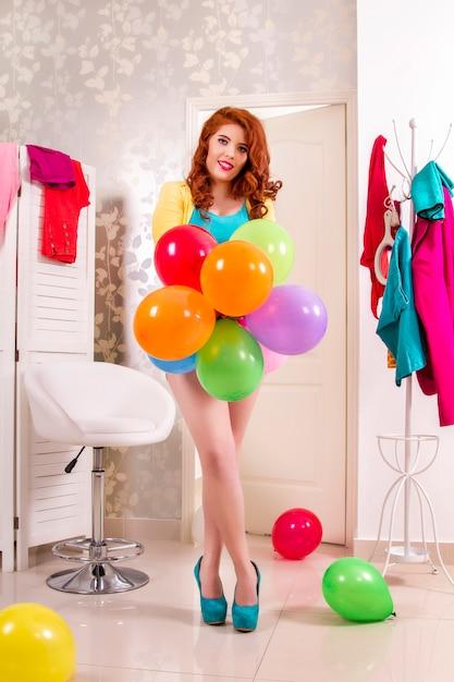 Vue d'une belle fille rousse dans sa chambre colorée. Photo Premium