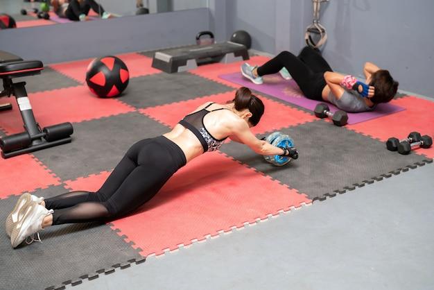 Vue de côté arrière d'une jeune femme en entraînement de sportswear avec roue ab sur fond de gym. Photo Premium