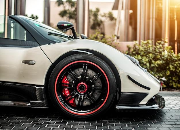 Vue de côté avant d'une voiture de sport grise, couleur argent avec roues rouges sur la route. Photo gratuit
