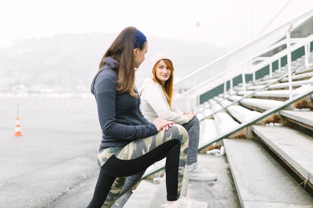 Vue de côté de deux athlètes féminines qui s'étend de la jambe sur un escalier en hiver Photo gratuit