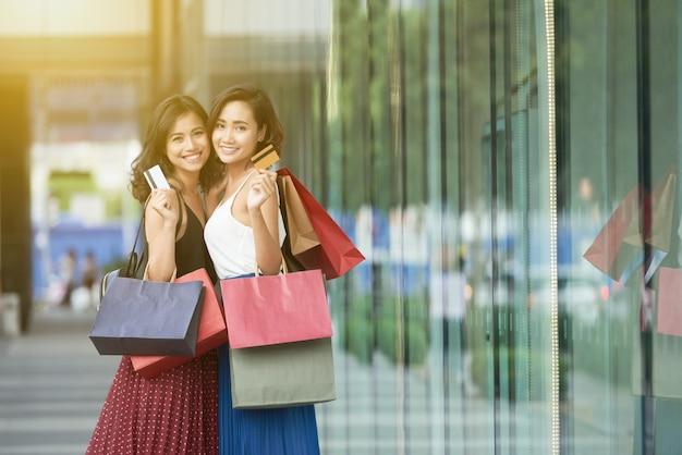 Vue de côté de deux dames shopping debout dans un centre commercial avec cartes de crédit Photo gratuit