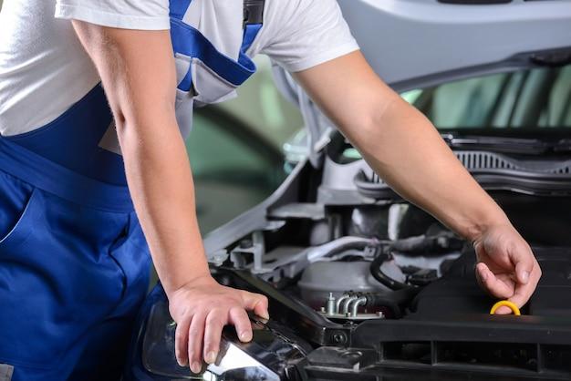 Vue de côté du mécanicien vérifiant l'huile moteur dans une voiture. Photo Premium